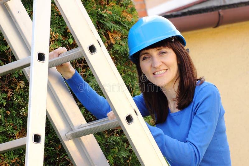 Χαμογελώντας γυναίκα στο μπλε κράνος που αναρριχείται στη σκάλα αργιλίου στοκ εικόνα