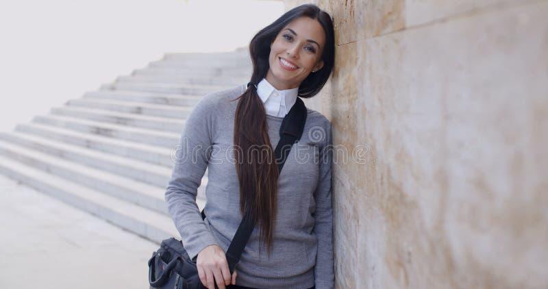 Χαμογελώντας γυναίκα στο πουλόβερ κοντά στον τοίχο που κοιτάζει στοκ εικόνα με δικαίωμα ελεύθερης χρήσης