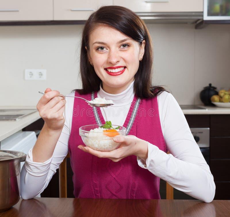Χαμογελώντας γυναίκα brunette που τρώει το βρασμένο ρύζι στοκ φωτογραφία