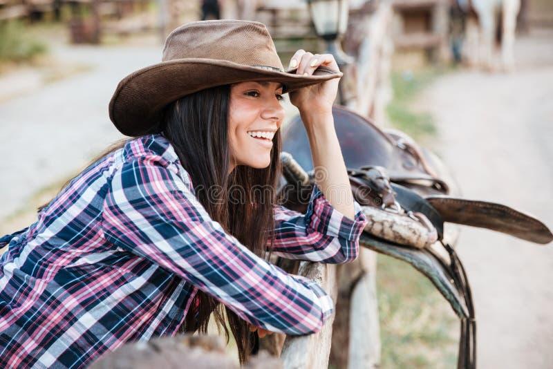 Χαμογελώντας γυναίκα cowgirl που κλίνει στο φράκτη στο χωριό στοκ εικόνα με δικαίωμα ελεύθερης χρήσης