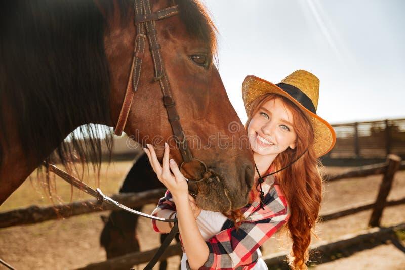 Χαμογελώντας γυναίκα cowgirl που στέκεται με το άλογό της στο αγρόκτημα στοκ φωτογραφία με δικαίωμα ελεύθερης χρήσης