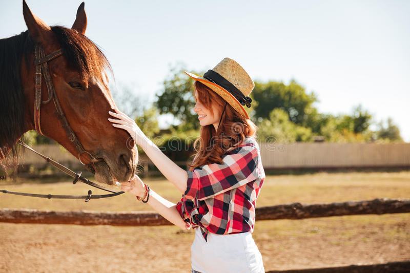 Χαμογελώντας γυναίκα cowgirl που φροντίζει το άλογό της στο αγρόκτημα στοκ φωτογραφίες με δικαίωμα ελεύθερης χρήσης