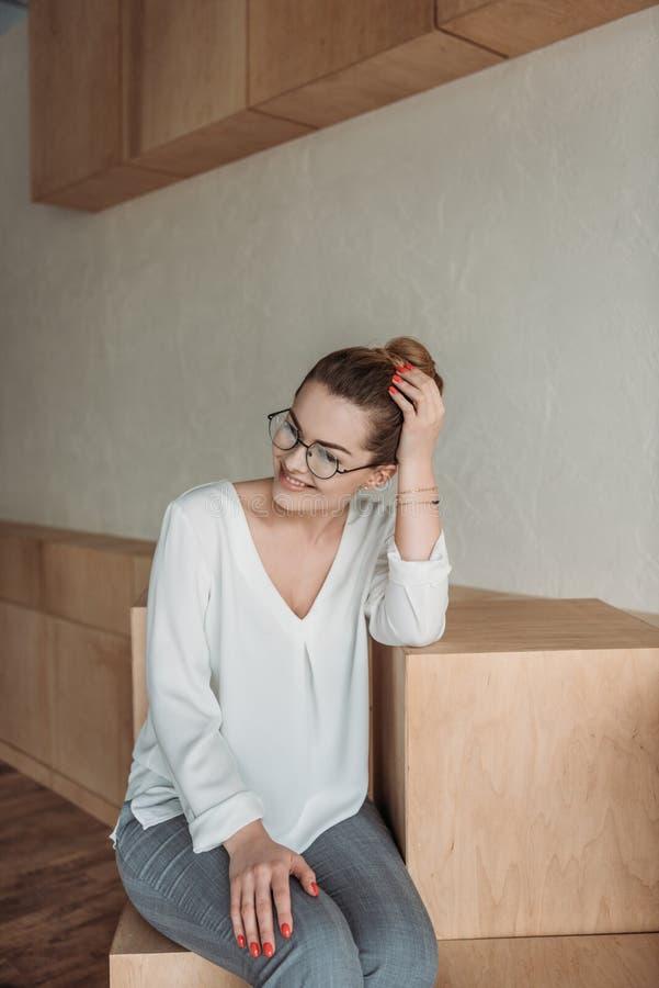 Χαμογελώντας γυναίκα eyeglasses που κάθεται στους ξύλινους κύβους στοκ φωτογραφία
