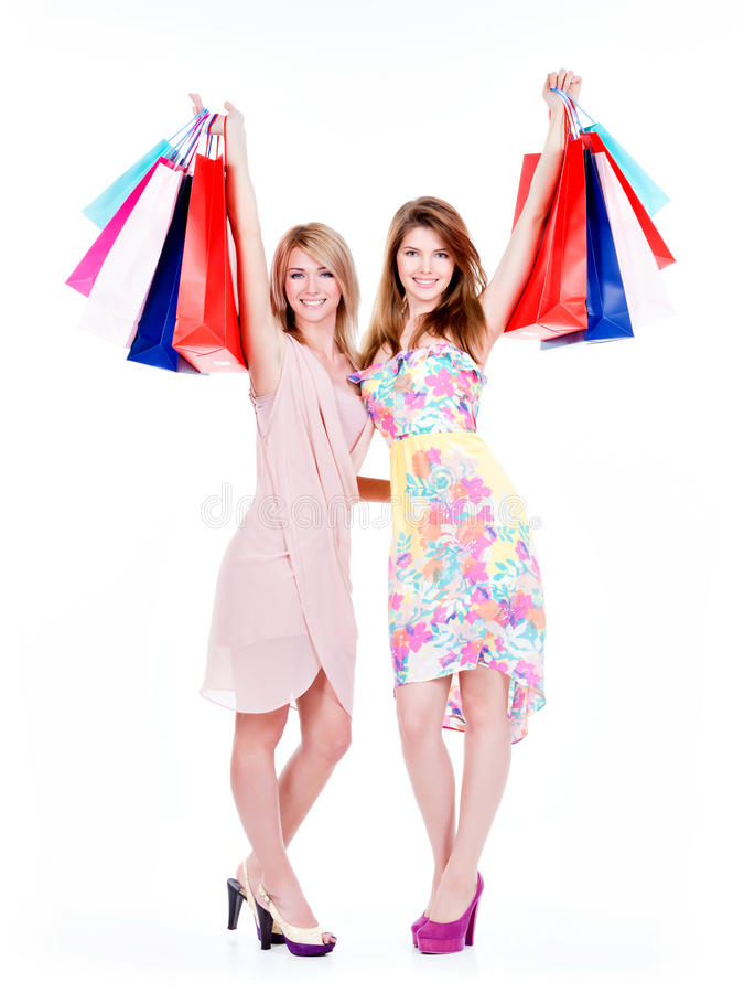 Χαμογελώντας γυναίκες που ανατρέφονται επάνω στις ζωηρόχρωμες τσάντες αγορών στοκ εικόνες