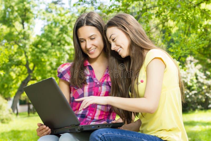Χαμογελώντας γυναίκες σπουδαστές που χρησιμοποιούν το lap-top στοκ εικόνες με δικαίωμα ελεύθερης χρήσης