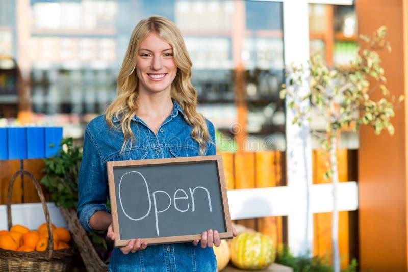 Χαμογελώντας γυναικείο προσωπικό που κρατά τον ανοικτό πίνακα σημαδιών στην υπεραγορά στοκ εικόνα