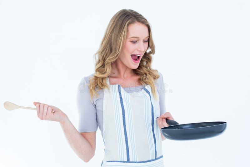 Χαμογελώντας εκμετάλλευση γυναικών που τηγανίζει το παν και ξύλινο κουτάλι στοκ εικόνες