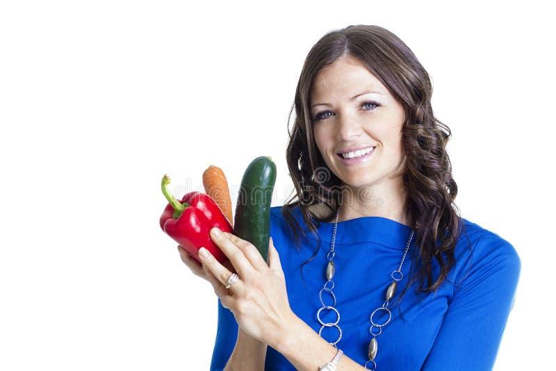 Χαμογελώντας ενήλικη γυναίκα που κρατά τα υγιή τρόφιμα στοκ φωτογραφίες