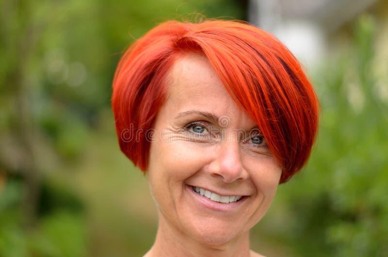 Χαμογελώντας ενήλικη Redhead γυναίκα ενάντια στη μουντή πρασινάδα στοκ εικόνα με δικαίωμα ελεύθερης χρήσης