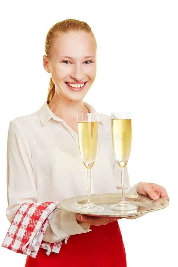 Χαμογελώντας εξυπηρετώντας σαμπάνια σερβιτόρων στοκ εικόνα