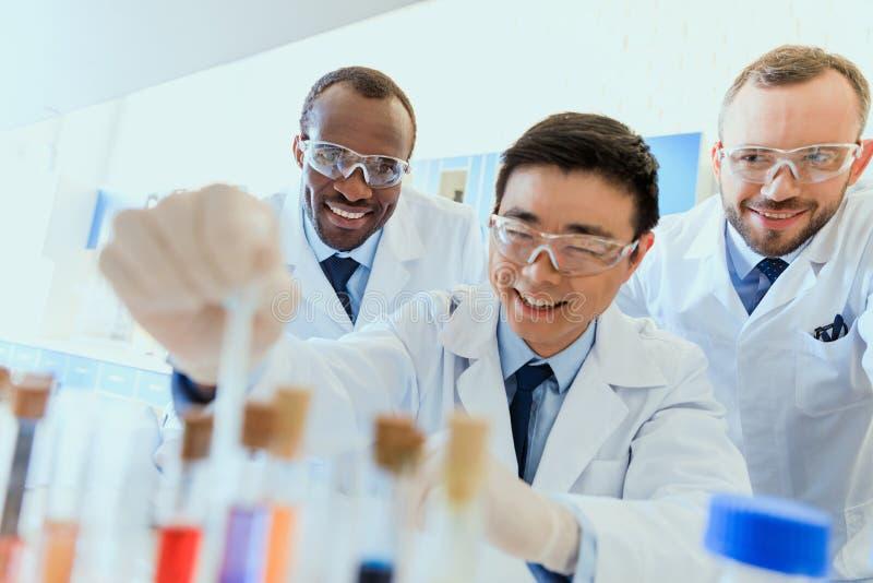 Χαμογελώντας επιστήμονες προστατευτικά eyeglasses που λειτουργούν μαζί στο χημικό εργαστήριο στοκ εικόνα με δικαίωμα ελεύθερης χρήσης