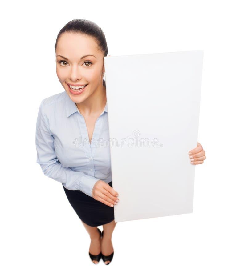 Χαμογελώντας επιχειρηματίας με το λευκό κενό πίνακα στοκ φωτογραφία