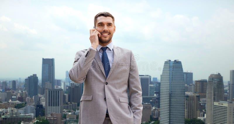 Χαμογελώντας επιχειρηματίας με το smartphone στην πόλη στοκ εικόνα με δικαίωμα ελεύθερης χρήσης