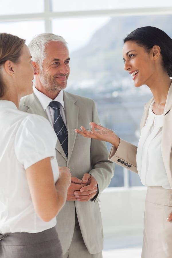 Χαμογελώντας επιχειρηματίας που λέει κάτι στους συναδέλφους της στοκ φωτογραφίες