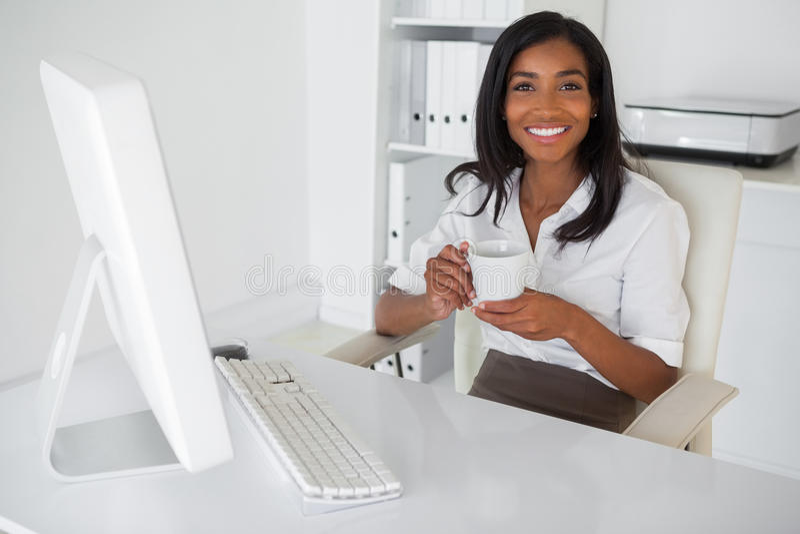 Χαμογελώντας επιχειρηματίας που έχει έναν καφέ στο γραφείο της στοκ φωτογραφία με δικαίωμα ελεύθερης χρήσης