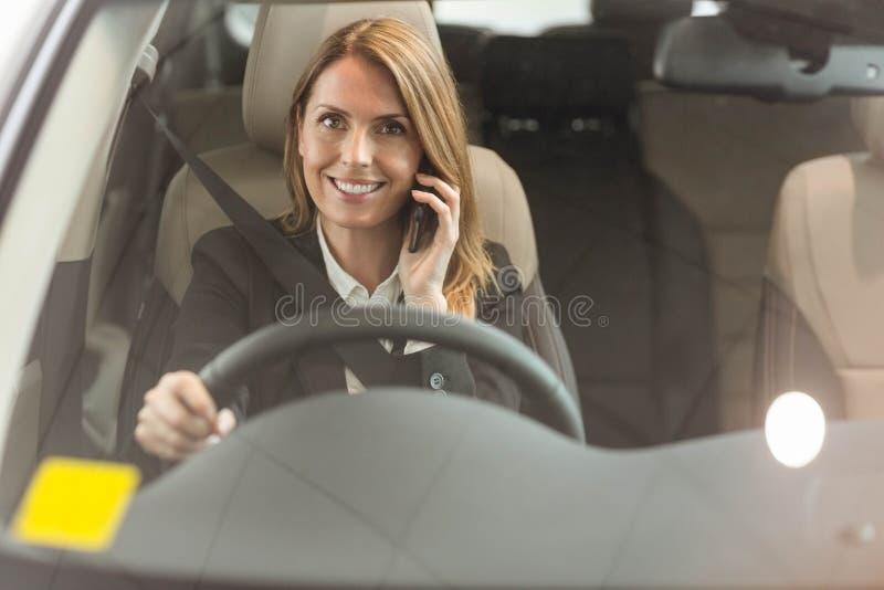 Χαμογελώντας επιχειρηματίας που έχει ένα τηλεφώνημα καθμένος σε ένα αυτοκίνητο στοκ φωτογραφία με δικαίωμα ελεύθερης χρήσης