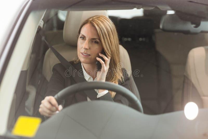 Χαμογελώντας επιχειρηματίας που έχει ένα τηλεφώνημα καθμένος σε ένα αυτοκίνητο στοκ φωτογραφίες