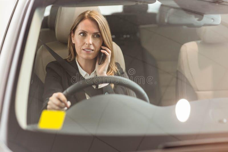 Χαμογελώντας επιχειρηματίας που έχει ένα τηλεφώνημα καθμένος σε ένα αυτοκίνητο στοκ εικόνες με δικαίωμα ελεύθερης χρήσης