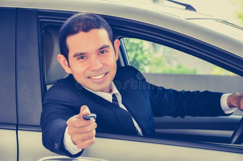 Χαμογελώντας επιχειρηματίας που δίνει ένα κλειδί αυτοκινήτων στοκ φωτογραφία με δικαίωμα ελεύθερης χρήσης