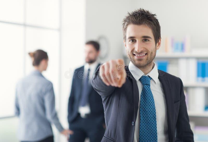 Χαμογελώντας επιχειρηματίας που δείχνει στη κάμερα στοκ φωτογραφία