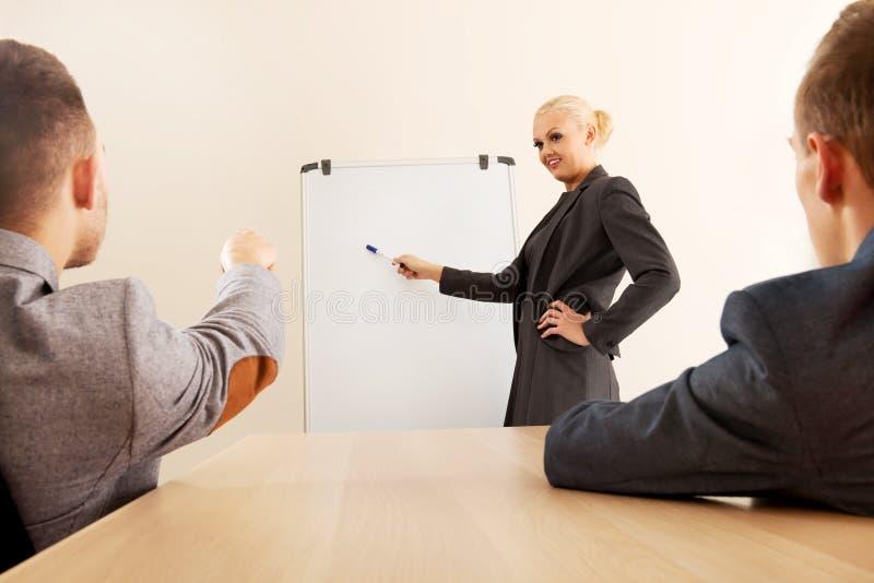 Χαμογελώντας επιχειρηματίας που επισύρει την προσοχή μια γραφική παράσταση για τους συναδέλφους της στο whiteboard στοκ εικόνες με δικαίωμα ελεύθερης χρήσης