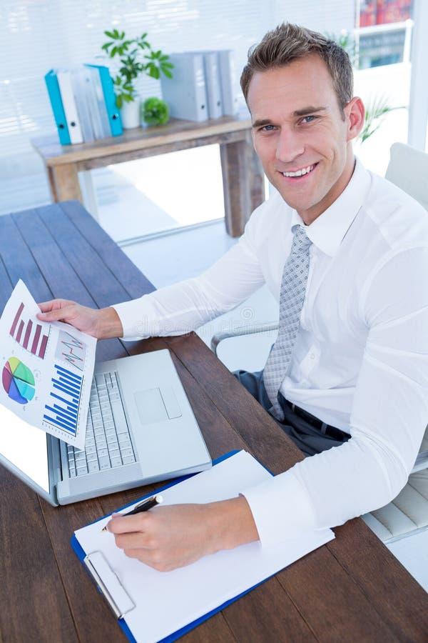 Χαμογελώντας επιχειρηματίας που εργάζεται με τα διαγράμματα ροής στοκ εικόνα