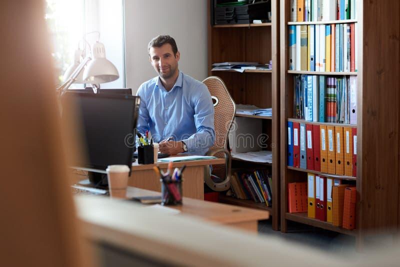 Χαμογελώντας επιχειρηματίας που εργάζεται στο γραφείο του σε ένα γραφείο στοκ εικόνες