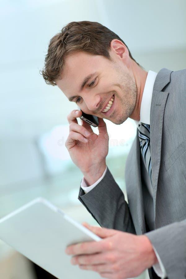 Χαμογελώντας επιχειρηματίας που κάνει επιχειρήσεις στο τηλέφωνο στοκ φωτογραφία με δικαίωμα ελεύθερης χρήσης