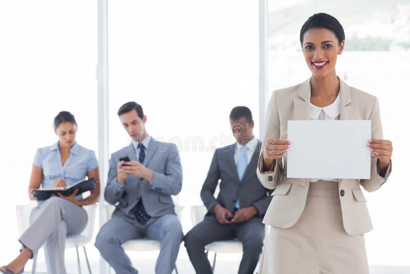 Χαμογελώντας επιχειρηματίας που κρατά μια κενή ειδοποίηση στοκ εικόνες