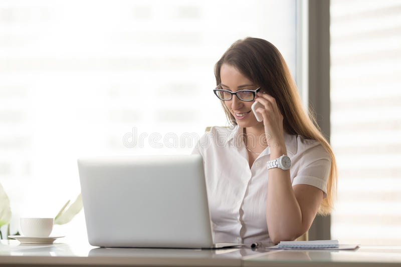 Χαμογελώντας επιχειρηματίας που μιλά στο τηλέφωνο χρησιμοποιώντας το lap-top, calli στοκ φωτογραφία με δικαίωμα ελεύθερης χρήσης