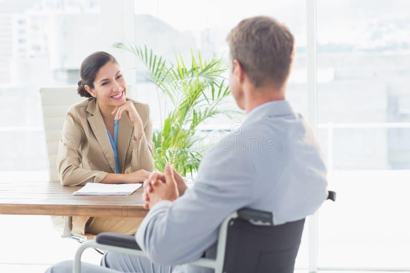 Χαμογελώντας επιχειρηματίας που παίρνει συνέντευξη από το με ειδικές ανάγκες υποψήφιο στοκ φωτογραφίες με δικαίωμα ελεύθερης χρήσης