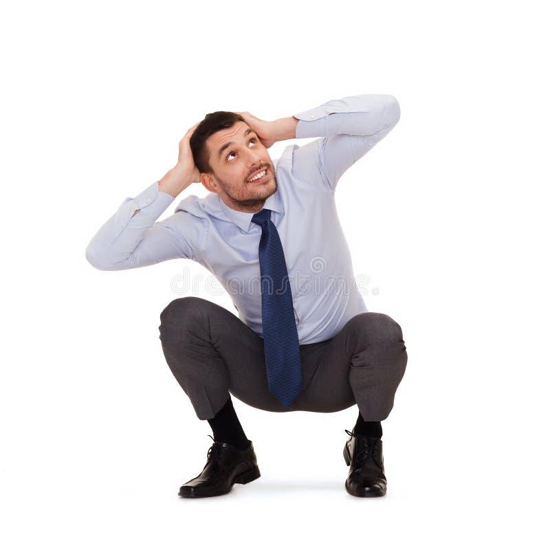 Χαμογελώντας επιχειρηματίας που σκύβει στο πάτωμα στοκ εικόνα