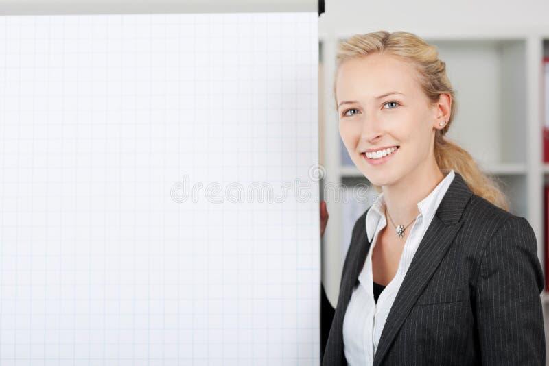 Χαμογελώντας επιχειρηματίας που υπερασπίζεται Flipchart στην αρχή στοκ εικόνες με δικαίωμα ελεύθερης χρήσης