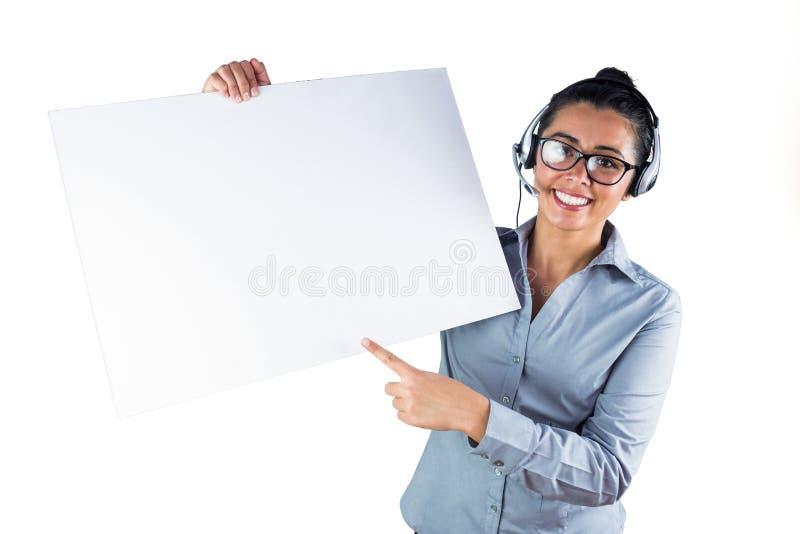 Χαμογελώντας επιχειρηματίας που φορά την κάσκα και το κράτημα του άσπρου φύλλου στοκ φωτογραφία