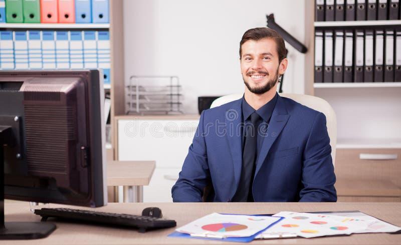 Χαμογελώντας επιχειρηματίας στο επιχειρησιακό κοστούμι στο χώρο εργασίας του στοκ φωτογραφίες με δικαίωμα ελεύθερης χρήσης