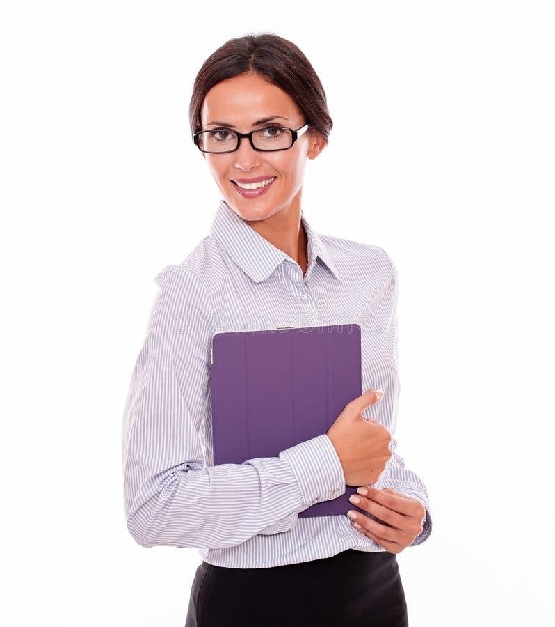 Χαμογελώντας επιχειρηματίας brunette που φέρνει μια ταμπλέτα στοκ εικόνα με δικαίωμα ελεύθερης χρήσης
