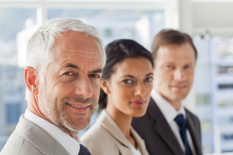 Χαμογελώντας επιχειρηματίες που κοιτάζουν με τον ίδιο τρόπο στοκ εικόνες