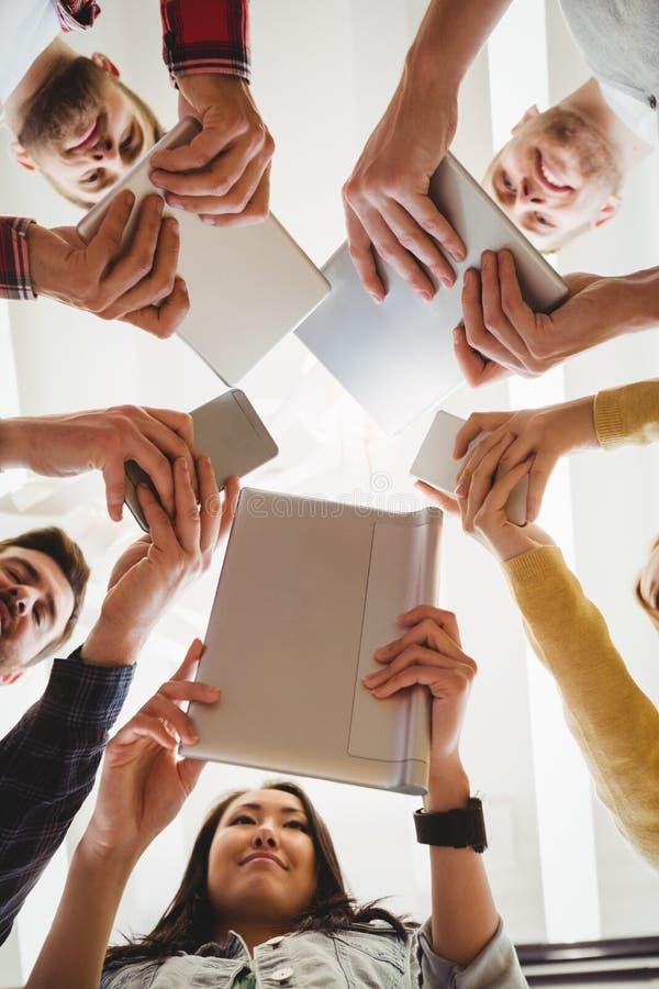 Χαμογελώντας επιχειρηματίες που χρησιμοποιούν τις τεχνολογίες στοκ εικόνες με δικαίωμα ελεύθερης χρήσης