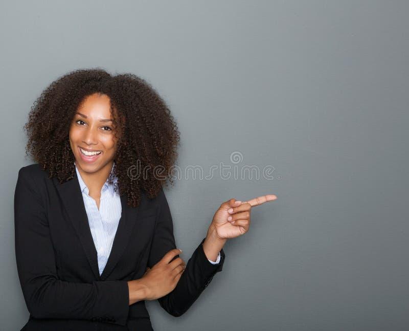 Χαμογελώντας επιχειρησιακή γυναίκα που δείχνει το δάχτυλο στοκ φωτογραφία