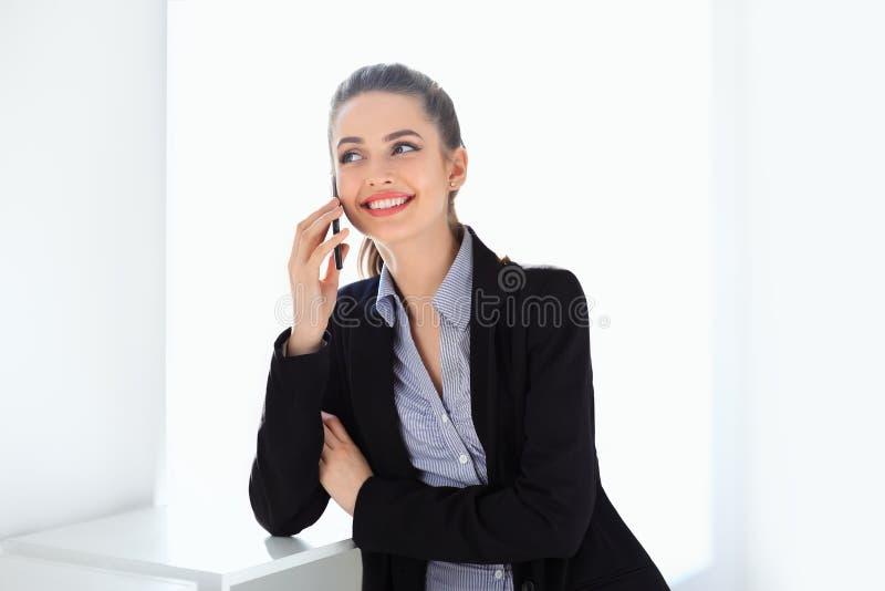 Χαμογελώντας επιχειρησιακή γυναίκα που μιλά στο κινητό τηλέφωνο στοκ φωτογραφία