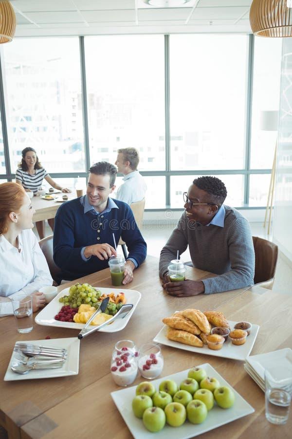 Χαμογελώντας επιχειρησιακοί συνάδελφοι που έχουν το πρόγευμα στην καφετέρια γραφείων στοκ φωτογραφίες
