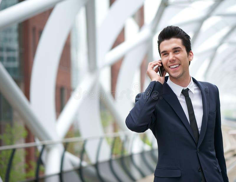 Χαμογελώντας επιχειρησιακό άτομο που μιλά στο κινητό τηλέφωνο στην πόλη στοκ εικόνα