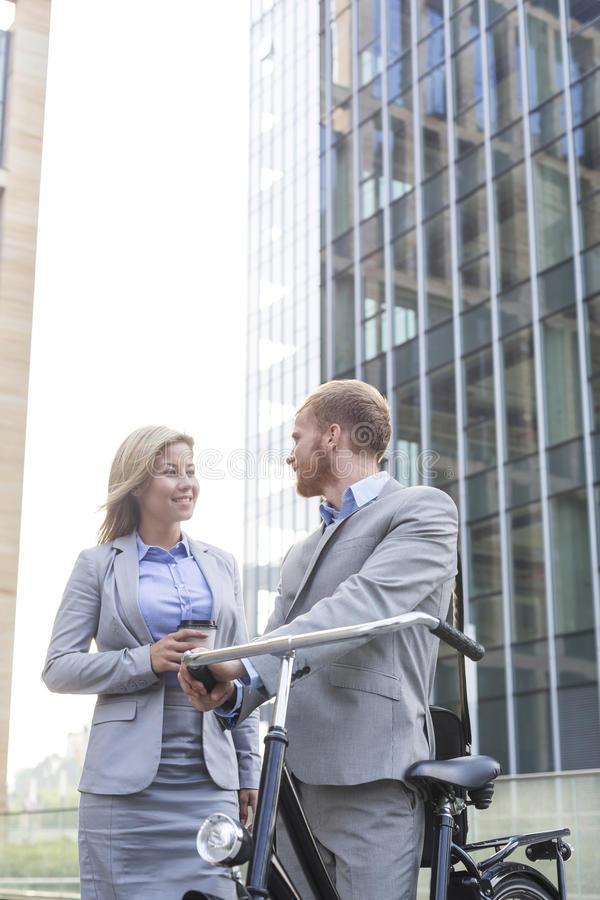 Χαμογελώντας επιχειρησιακό ζεύγος που μιλά έξω από το κτίριο γραφείων στοκ εικόνες