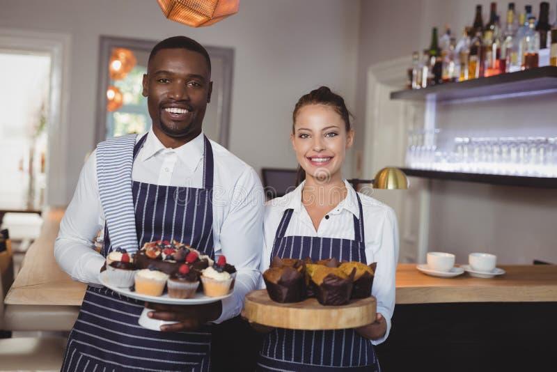 Χαμογελώντας επιδόρπια εκμετάλλευσης σερβιτόρων και σερβιτορών στο μετρητή στοκ εικόνες