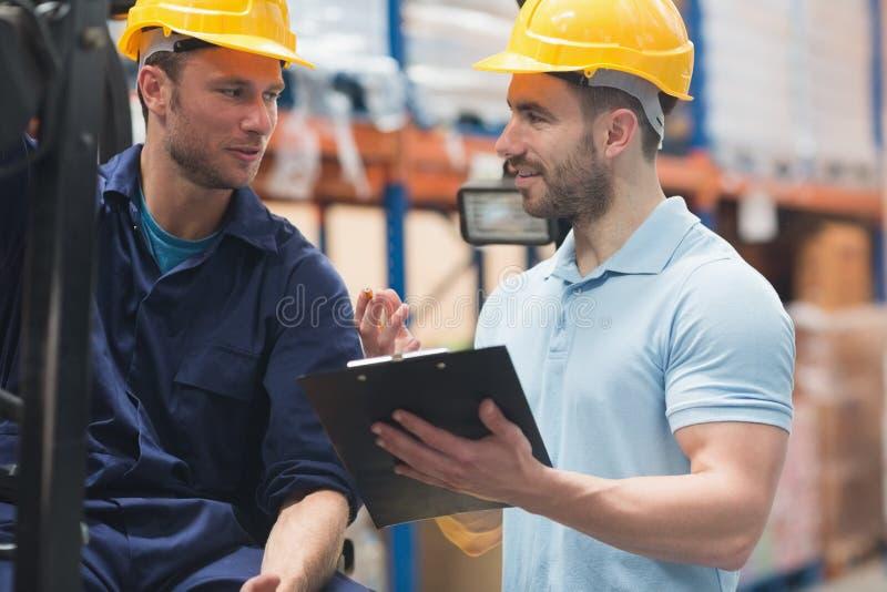 Χαμογελώντας εργαζόμενοι αποθηκών εμπορευμάτων που μιλούν από κοινού στοκ φωτογραφία με δικαίωμα ελεύθερης χρήσης