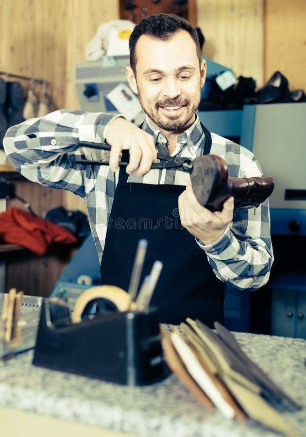 Χαμογελώντας εργαζόμενος ατόμων που εργάζεται στην αποκατάσταση των μποτών στοκ εικόνες