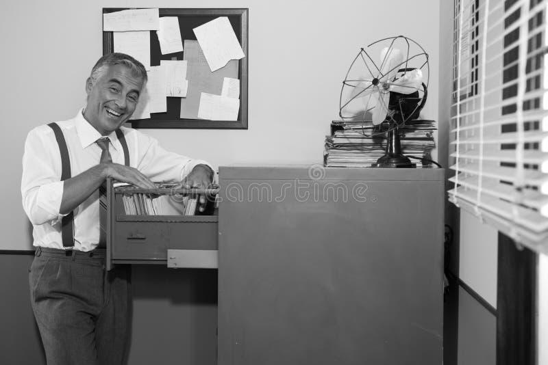 Χαμογελώντας εργαζόμενος γραφείων που ψάχνει για ένα αρχείο στοκ εικόνες με δικαίωμα ελεύθερης χρήσης