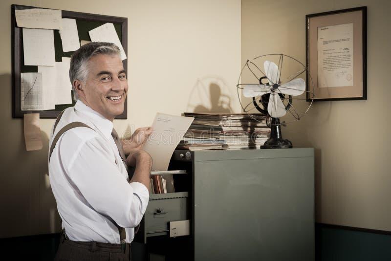 Χαμογελώντας εργαζόμενος γραφείων που ψάχνει για ένα αρχείο στοκ εικόνα