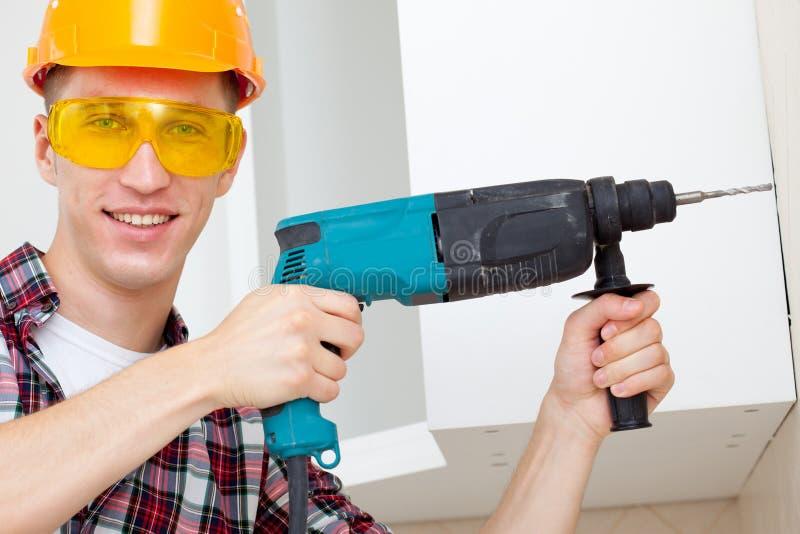 Χαμογελώντας εργαζόμενος με το βράχος-τρυπάνι στοκ φωτογραφία
