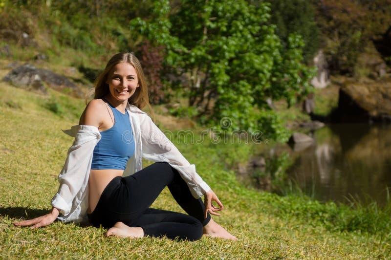 Χαμογελώντας λευκιά νέα γυναίκα που κάνει τη γιόγκα στοκ εικόνες